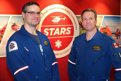 STARS pilot Andrew Davidson, left, and paramedic Troy Pauls are shown at Manitoba Ag Days at the Keystone Centre. The air ambulance service expects to soon roll out a subscription-based model of its smartphone app, which will allow STARS to fly to a patient's location without a description of where they are.