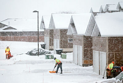 Workers clear snow from driveways in a condo development on Camryn Lane in Brandon's south end during flurries on Wednesday morning.