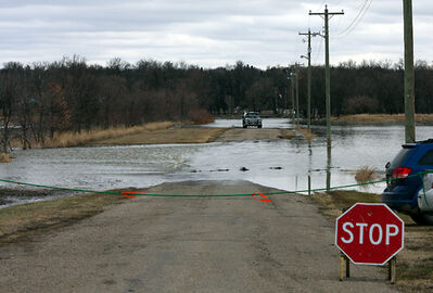 Floodwater from the Assiniboine River races over the entrance road to Turtle Crossing Campground on Monday.