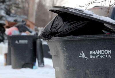 Overflowing garbage bins in a back lane behind MacDonald Avenue on Thursday. Brandon residents who don't bring their garbage bins back into their yard after back lane pickup will receive two warnings before a fine is handed out for a third offence.