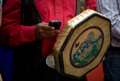 Chief Roger William, of the Xeni Gwet'in First Nation, checks his messages while holding a traditional drum during a news conference in Vancouver, B.C. Thursday.