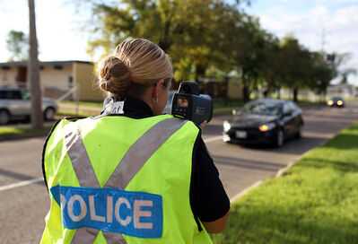 Const. Alice Potter of the Brandon Police Service traffic unit monitors traffic using a laser speed gun in a school zone on 26th Street on Wednesday morning. Several drivers got off with warnings for travelling faster than the new 30 km/h speed limit.