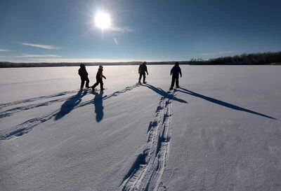 Kids blaze a trail across snow-covered Williams Lake in Turtle Mountain Provincial Park.