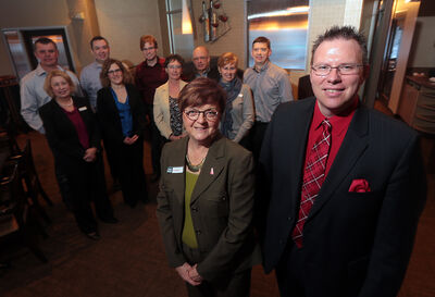 Wendy Bulloch, past board member and chair of the Manitoba Heart and Stroke Foundation, and Doug Adams, recipient of a mechanical heart value, right, are guests of honour with members of the Total Eye Care Centre, gathered in background, during a donor recognition event at Remington's Seafood and Steakhouse on Wednesday.