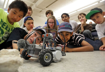 Kids taking part in the annual Mini U summer camp at Brandon University admire a remotely operated robot on Thursday. For the first time, the summer camp is offering a Mission to Mars Camp, during which the students design, prepare and execute a simulated mission.