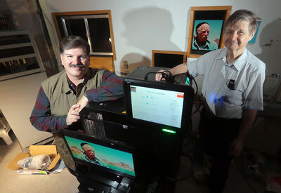 Brandon Film Festival Inc. Mark Delmage and Ken McKenzie-Cochrane pose with the new digital projector, which will allow the Evans Theatre to start showing digital features. (Bruce Bumstead/Brandon Sun)