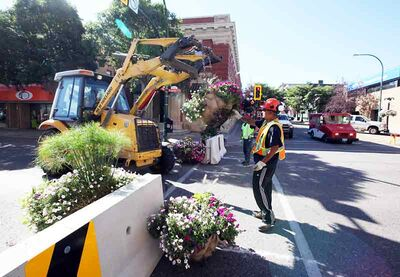 City workers install plants and flower baskets on Rosser Avenue between Ninth and 10th streets in August 2011 for a pedestrian mall. The initiative received mixed reviews and was not renewed the following summer or      this year.