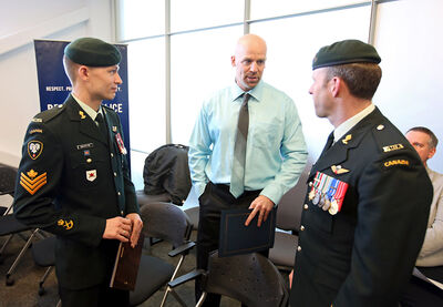 Sgt. Michael MacIntyre with the 1st Regiment Royal Canadian Horse Artillery speaks with Sgt. Mike Tosh with the Brandon Police Service as well as Lt.-Col. Stew Taylor, commanding officer for 1RCHA, after the Brandon Police Service awards ceremony at their headquarters on 10th Street on Thursday. MacIntyre received the Citizen Recognition Award and Tosh was given a Favourable Notice after both helped to stop a young woman from jumping from the First Street  bridge. Two citizens and six police officers were honoured with awards.