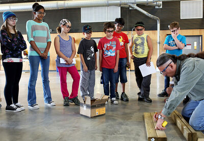 Kids taking part in a two-week carpentry summer camp, hosted by the Assiniboine Community College and funded by the province's Building for Tomorrow pilot program, watch as instructor Randy Kaskiw shows them how to start building a dog house.
