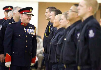 Former Brandon Police Service chief Keith Atkinson chats with a graduate during the Assiniboine Community College police studies class final inspection and drill ceremonies in 2012.
