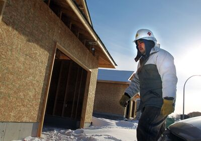 Joaquin Pena bundles up against the cold while working on a construction site in the city's southwest corner earlier this month. A boom in residential construction is not quite enough to make up for a shortfall in other Brandon construction.