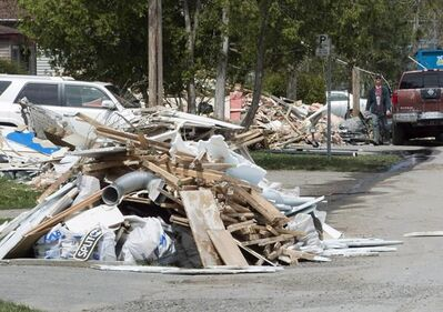 Flood debris piles up on a street Monday, May 15, 2017 in Laval, Que. as residents clean up as the flood waters recede. Quebec's public security minister says waters are continuing to recede from flood-stricken areas of the province. THE CANADIAN PRESS/Ryan Remiorz