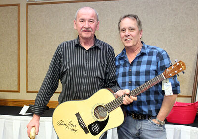 Charlie Major poses with Bob Wison, who won the autographed guitar.
