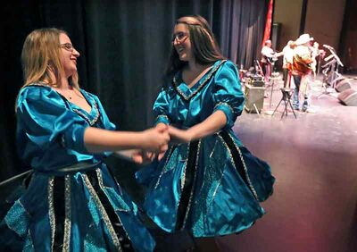 Kelsey McLennan, left, and Calista Sainsbury dance backstage at the Métis pavilion on Friday evening.