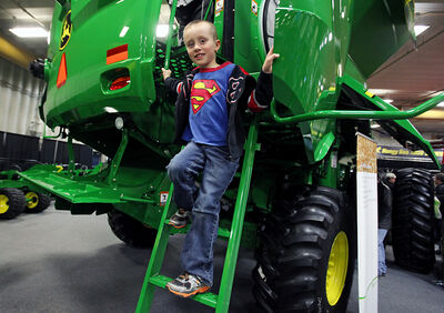 Jakob Erlandson climbs down from a John Deere combine during the Manitoba Ag Days at the Keystone Centre on Wednesday.
