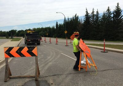 A worker hauls away signs from First Street North near Kirkcaldy Drive on Thursday afternoon, as he helps re-open that stretch of First Street. One lane in each direction has been opened to travel, some 20 days after it slipped under the waves of the rising Assiniboine River.