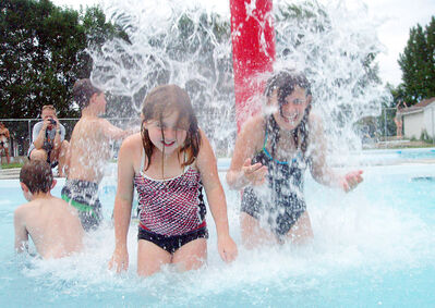 Ellie Beare and Cassandra Hamilton play under a fountain of water at the Wawanesa and District Water Park on Monday.