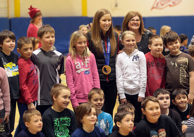 Olympic gold medallist Kaitlyn Lawes poses for a photo with students at Meadows School on Monday morning.