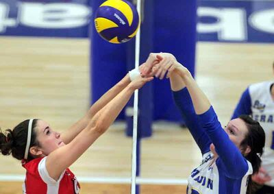 Alicia Perry, left, of the Winnipeg Wesmen and Meaghan Robertson of the Brandon University Bobcats meet at the net during CIS women's volleyball competition Thursday evening at the Healthy Living Centre. The Wesmen won in straight sets.