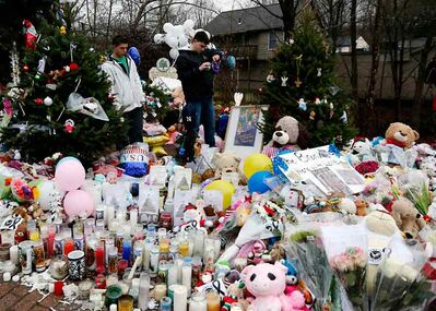 Ryan Bartolotta, 17, right, and Ray Massi, 18, light candles that were put out by rain at a makeshift memorial in the Sandy Hook Village of Newtown, Conn., as the town mourns victims killed in a school shooting on Monday.