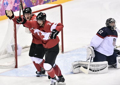 Canada's Jamie Benn celebrates with Jeff Carter, left, after scoring the first goal against United States' goaltender Jonathan Quick during second period hockey semifinal action at the 2014 Sochi Winter Olympics in Russia on Friday.