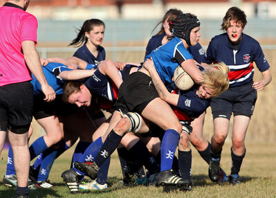 Kendra Roberts of the Souris Sabres knocks Hailey Rapsky of the Minnedosa Chancellors to the ground while running the ball during a Westman High School Rugby girls' game at John Reilly Field on Friday evening. Souris won 41-5.
