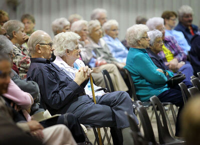 Audience members listen to the Mennonite Central Committee fundraising auction at the Keystone Centre on Saturday afternoon.