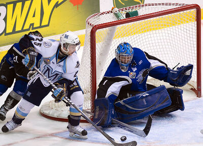 Saint John Sea Dogs goalie Jacob DeSerres, right, makes a save on a wrap around attempt by Mississauga St. Michaels Majors forward Riley Brace during Sunday's Memorial Cup final.