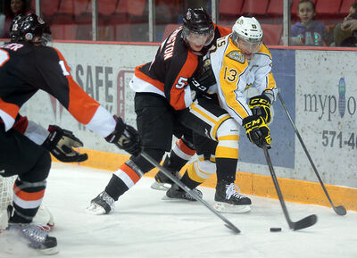 Brandon's Rihards Bukarts plays the puck while being held by Medicine Hat's Tyler Lewington Wednesday.