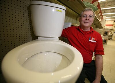 Shawn Ansley of Home Hardware shows off one of their American Standard dual flush toilets at the Victoria Avenue store in 2009.