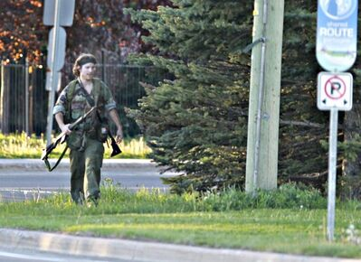 A heavily armed man that police have identified as Justin Bourque walks on Hildegard Drive in Moncton on Wed. June 4, 2014 after several shots were fired in the area. THE CANADIAN PRESS/Moncton Times & Transcript - Viktor Pivovarov / telegraphjournal.com