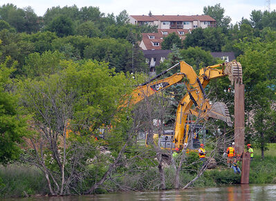City crews work to shore up dikes on the Assiniboine River near Kirkcaldy Drive ahead of an expected rise in water levels in coming days on Wednesday afternoon.