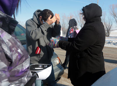 Students smudge with smoke from sage, cedar and tobacco prior to a noon-hour protest outside Crocus Plains on Monday.