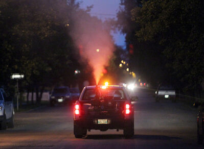 City crews spray malathion along Louise Avenue near 12th Street earlier this month. A third round of spraying is scheduled for tonight.