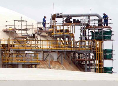 Workers are perched atop one of the storage tanks surrounding the Koch Industries fertilizer plant in September.