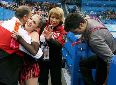 Paige Lawrence hugs coach Lyndon Johnston, a Hamiota native, with coach Patty Hole of Virden and Rudi Swiegers (far right) Tuesday at the Winter Olympic Games in Sochi, Russia.