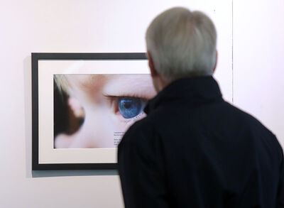"A visitor looks at one of the photos in the ""Man-Up Against Suicide"" exhibit, which will be on display at the Tommy McLeod Curve Gallery until June 8."