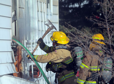 Firefighters work to control a fire in the walls of a home on the 600-block of 12th Street shortly after 5 pm. on Wednesday. Officials say two family pets died in the blaze. The cause of the fire has yet to be determined.