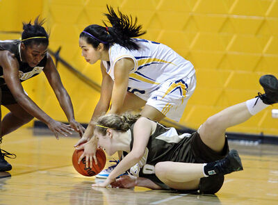 Brandon's Kaela Cranston (centre) scoops up a loose ball under pressure from Manitoba Bisons' Maria Pawlyshyn (right) and Mubo Ilelabyoe during Canada West women's basketball action on Friday night at the Brandon University gym.