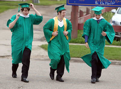 Cody Oliver, left, Jonathan Bertram and Joel Durand cross the street prior to École secondaire Neelin High School's graduation ceremony at the Western Manitoba Centennial Auditorium on Tuesday.