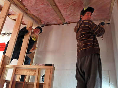 Braydon Drover (right) and Rodney Barker work at the housing complex currently under construction by Youth for Christ on Fifth Street.