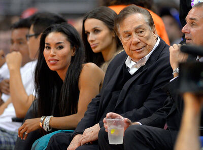 Los Angeles Clippers owner Donald Sterling, right, and V. Stiviano, left, watch the Clippers play the Sacramento Kings during an NBA basketball game in Los Angeles in October 2013. NBA commissioner Adam Silver banned Sterling for life and fined him $2.5 million after a recorded conversation in which Sterling made several racist comments to Stiviano went viral last weekend.