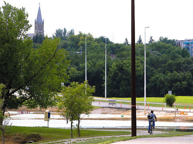 A cyclist makes his way along a portion of the pedestrian walkway recently resurfaced from receding floodwaters along First Street North.