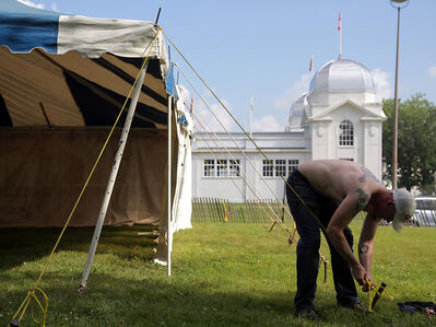 Nathan Rogers works on a tent at the Keystone Centre forest site of the Brandon Folk, Music and Art Festival on Tuesday afternoon. The annual weekend music and art festival kicks off this Friday.