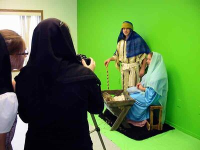 "Students make a digital video of the Christmas story against a ""green screen."""