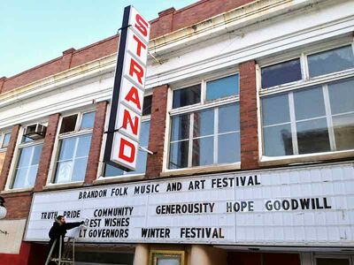 Strand Project volunteer Kevin Bertram braves the elements to place a supportive message on the marquee sign of the historic Strand Theatre in the Downtown HUB earlier this week. The Lieutenant Governor's Winter Festival is underway.