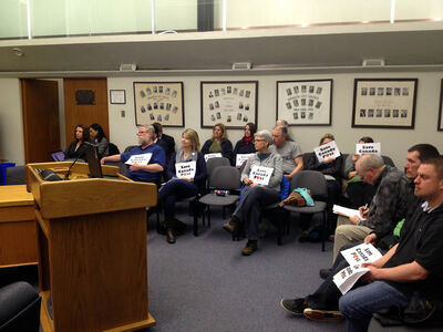 """Members of the gallery hold up """"Save Canada Post"""" signs as Brandon City Council discussed Canada Post's plan to phase out door-to-door delivery on Monday night."""