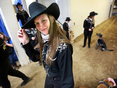 Jen Miller, from Nanaimo, B.C., tips her hat before taking to the main arena for the first SuperDogs show at the Royal Manitoba Winter Fair on Monday.