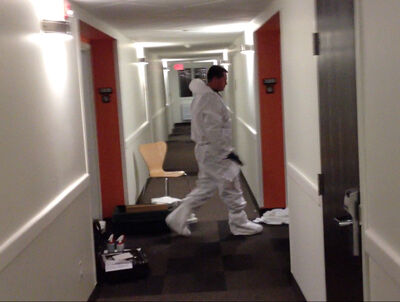 A forensic identification officer walks between two rooms at the Motel 6 on the Trans-Canada Highway in Brandon in this still from a video. Police are investigating a reported stabbing death at the hotel.