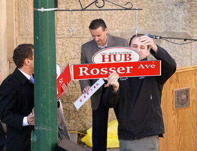 Corey Roberts, right,  and Coun. Vince Barletta (Rosser) hang signs at 10th Street and Rosser Avenue with the new branding logo.